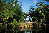 Macapa, Brazil. Well-built riverside caboclo shack house with reflection in bright sunshine.