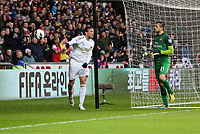 Pictured: An angry Michu of Swansea (L) hits the ball away after shooting off target while Arsenal goalkeeper Lukasz Fabianski looks on bemused (R). Saturday 16 March 2013<br />