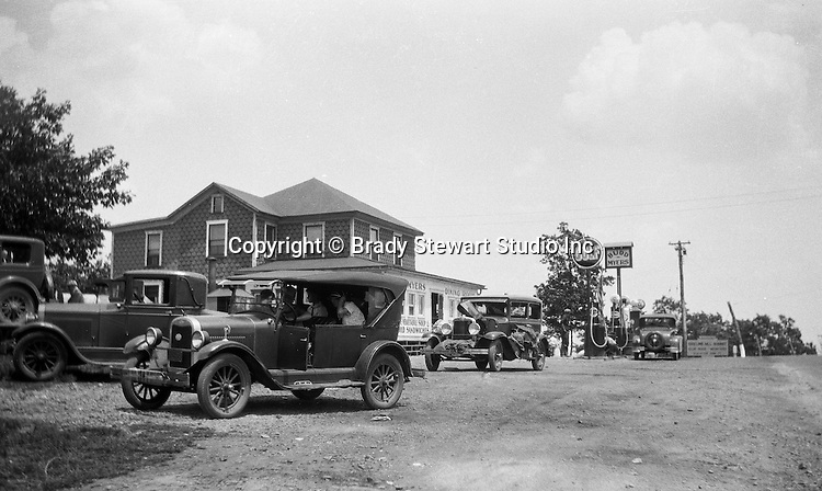 Harrisonville PA: The Stewart's taking a break while driving along Route 30 in Fulton County.  The Stewart's 1929 Chevy Coach and other cars stopped for gas at Bud Myers Gulf on Route 30 - 1931.