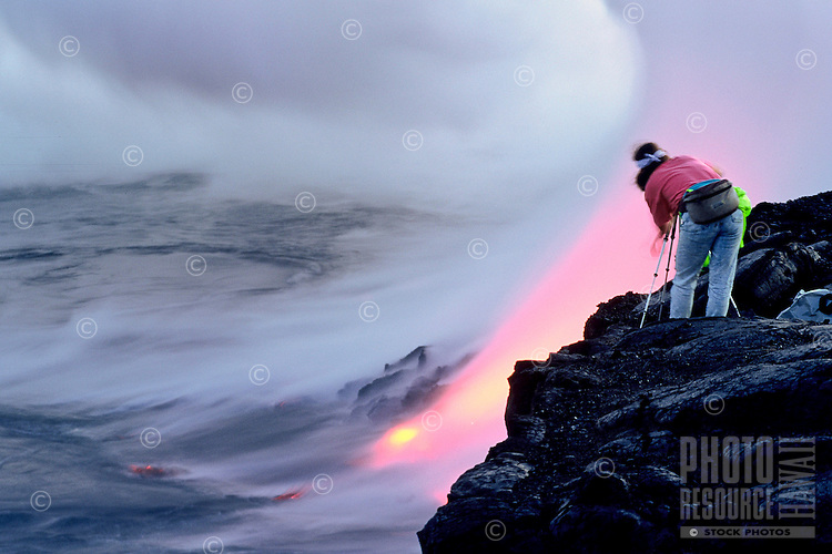 Photographer shooting lava flowing to the sea from Kilauea Volcano, Big Island of Hawaii