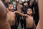 Muslim community Bradford UK. Children boys beating their chest in ritual self flagellation 2019 2010s. Day of Ashura parade Shia Muslims remember the martyrdom of Hussain, who was killed in the desert of Karbala in today's Iraq in A.D. 680. Shiite Muslims believe that Hussain was their third imam – a line of 12 divinely appointed spiritual and political successors.