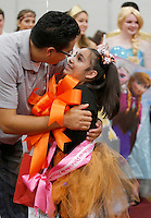 "NWA Democrat-Gazette/DAVID GOTTSCHALK   Andrea ""Isa"" Perez, a first grade student from Tyson Elementary School, is hugged by her father Antonio Friday, November 6, 2015, after she received a trip to Disney World during a special event pep rally at Springdale High School. Isa received the trip through the Make A Wish Foundation Mid-South Chapter with funds raised by the student organization DECA at the High School."