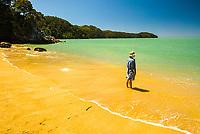 Young woman on beautiful, golden beach on Abel tasman Coastal Track, Abel Tasman National Park, Nelson Region, New Zealand, NZ
