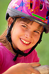 portrait of smiling young girl wearing bicycle helmet
