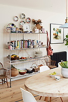 In the kitchen dining room, an antique bread stand makes a perfect shelving unit to display books, ceramics and other items.
