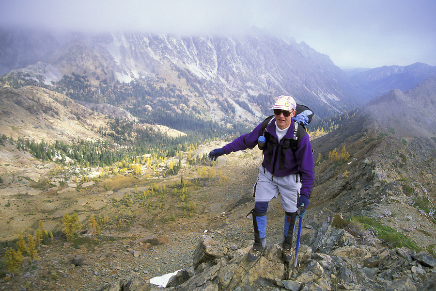 Man scrambling along ridge, Alpine Lakes Wilderness, Wenatchee National Forest, Cascade Mountains, Washington