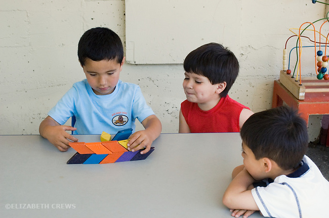 "Berkeley CA  Four-year-old experimenting with pattern blocks, friends in ""onlooker play"" watching him at bilingual Spanish-English preschool"