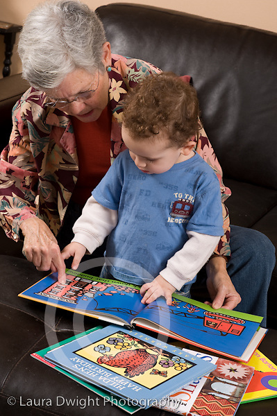 2 year old toddler boy at home with grandmother interaction read to from picture book language development grandmother talking and pointing to picture vertical she takes care of him when parents work