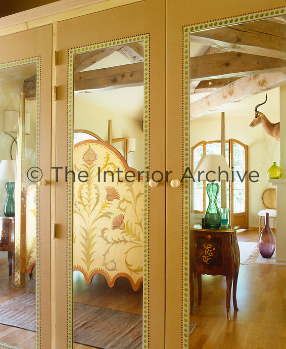 The ornate hand-painted bed is reflected in the mirrored cupboards of the bedroom