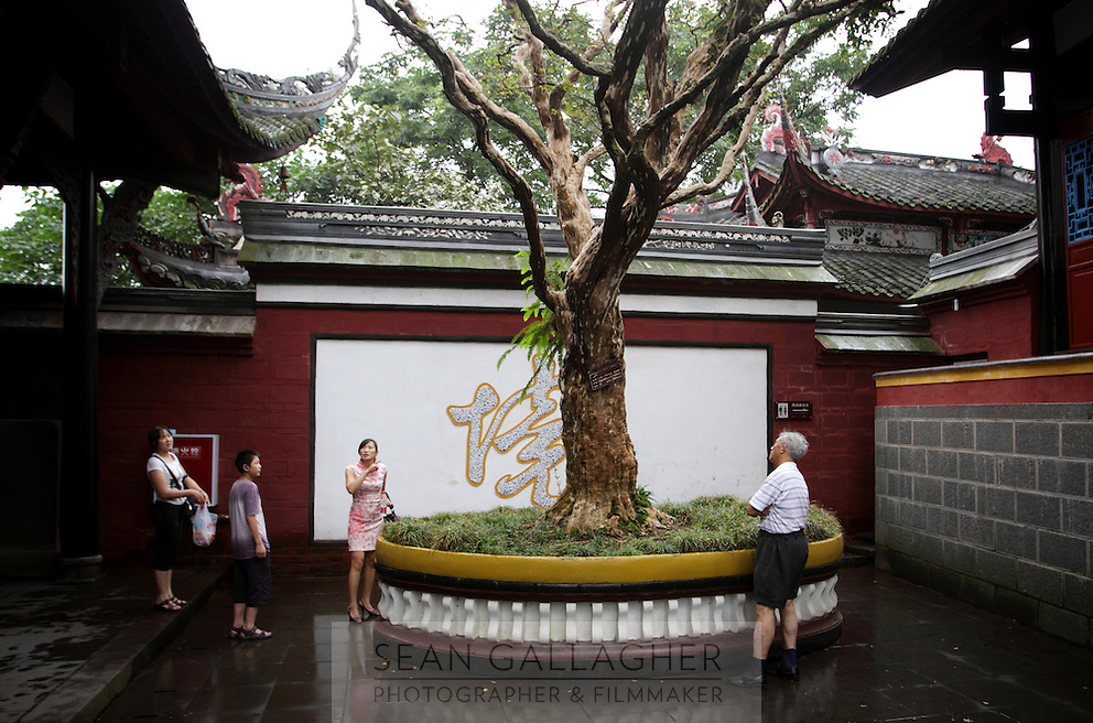 "Visitors look at a tree in a temple within the Dujiangyan Irrigation System. The system is regarded as an ""ancient Chinese engineering marvel."" By naturally channeling water from the Min River during times of flood, the irrigation system served to protect the local area from flooding and provide water to the Chengdu basin. Sichuan Province. 2010"