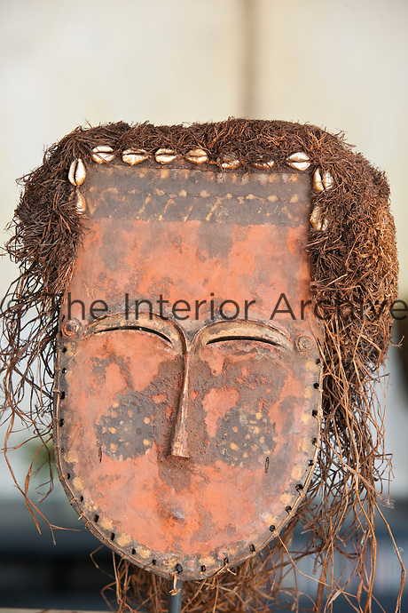Grass and shells make up the hair in this Congo mask called Lele, part of a large collection displayed throughout the house