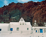 GREECE, Santorini, Akrotiri, white chapel with blue doors against the red rock at Red Sand Beach