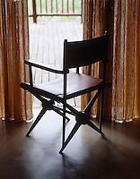 A leather director's chair looks out onto one of the terraces
