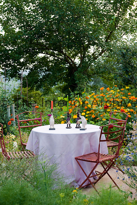 Figurine candle holders on a garden table covered with a tablecloth surrounded by bright red garden chairs