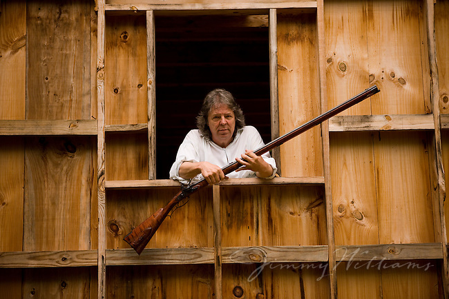 North Carolina gunmaker, Bobby Denton, poses in his workshop window with one of his handmade rifles.