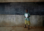 "A boy holds a sign for the letter ""K"" during a class in the Catholic Church-sponsored St. Daniel Comboni Primary School in Lugi, a village in the Nuba Mountains of Sudan. The area is controlled by the Sudan People's Liberation Movement-North, and frequently attacked by the military of Sudan. The church has sponsored schools and health care facilities throughout the war-torn region."