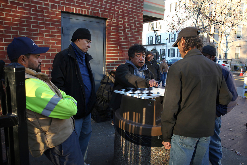 (171128RREI2281) El Rana playing in center at La Esquina where Latinos have gathered for decades at the corner of Mt. Pleasant St. and Kenyon St. NW. to play checkers (damas). Washington DC.  Nov. 28 ,2017 . ©  Rick Reinhard  2017     email   rick@rickreinhard.com