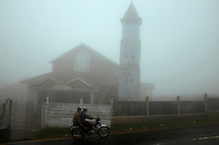 Men pass by the Presbyterian Church (built in 1845) on a motorcycle in Cherrapunji located in East Khasi Hills - the wettest place on Earth,  in north east of India. Arindam Mukherjee