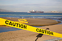 Caution tape cordons off the Crissy Field beach while a container ship navigates the San Francisco Bay near Alcatraz (11/12/07). The yellow line in the water is an oil spill containment boom. On November 7, 2007 the Cosco Busan container ship spilled an estimated 58,000 gallons of bunker fuel into San Francisco Bay after striking a tower of the San Francisco-Oakland Bay Bridge.
