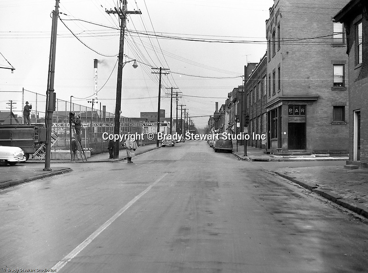 Pittsburgh PA:  An accident site on the North Side at Chateau Street and Western Avenue where a Railway Express truck knocked out traffic lights - 1953.  Policeman directing traffic while contractor repairs the traffic signals