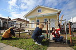 "(L-r) Barbara Blinderman, 74, Cheryl Levi, 62, and Bobbi Michaels, 60, ""voluntourists"" from the Am Shalom synagogue in Glencoe, Illinois, scrape rust off the fence outside the new home of Aniece ""Mrs.Gibbs,"" 89, in the Hollygrove section of New Orleans, Louisiana on March 11, 2008.  Gibbs survived Hurricane Katrina when a neighbor rescued her and currently lives in a FEMA trailer equipped for the disabled while awaiting the completion of her home."