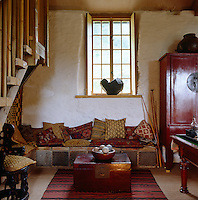 A collection of Turkish and African cushions on a tiled bench in a corner of the living room with a Chinese red lacquer cupboard and a chest for a coffee table