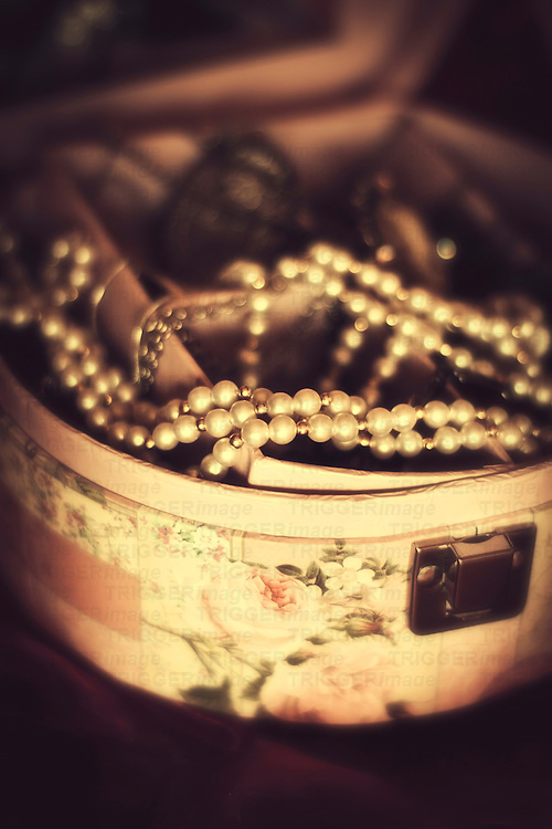 An old pearl necklace laid on old retro casket with roses