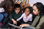 Education Preschool 3-4 year olds group of two girls and a boy read to by female teacher