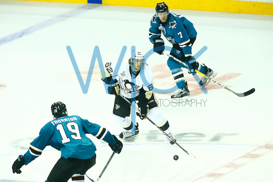 Carl Hagelin #62 of the Pittsburgh Penguins skates through Paul Martin #7 and Joe Thornton #19 of the San Jose Sharks during game three of the Stanley Cup Final at the SAP Center in San Jose, California on June 4, 2016. (Photo by Jared Wickerham / DKPS)