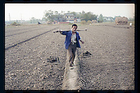 A Chinese peasant carries fertile mud to his farmland at a village in Jiangsu province, China, 1998.