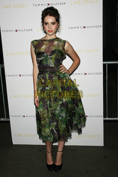 "Felicity Jones.The New York Premiere of ""Like Crazy"" at the Landmark Sunshine Cinema, New York, NY, USA..October 18th, 2011.full length dress hand on hip green brown sheer sleeveless leaves leaf print hair up.CAP/LNC/TOM.©TOM/LNC/Capital Pictures."