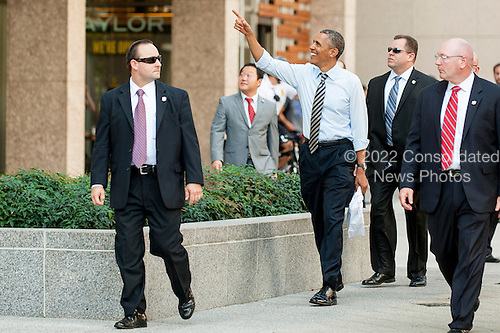 United States President Barack Obama waves to onlookers at Taylor Gourmet on Pennsylvania Avenue after walking from the White House for a take-out lunch. The reason he gave was they are starving and the establishment is giving a percent discount to furloughed government workers as an indication of how ordinary Americans are looking out for one another.<br /> Credit: Pete Marovich / Pool via CNP