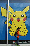 """May 9, 2010 - Tokyo, Japan - A young Japanese boy walks past a poster featuring a video game Nintendo's Pokemon character at the official Pokemon store in Tokyo on May 9, 2010. Nintendo recently announced that the DS handheld device had become the best selling gaming handheld of all time, with a total of 129 million units sold. The DS 'family' have surpassed the """"Game Boy"""" series which hit 118 million over two decades."""