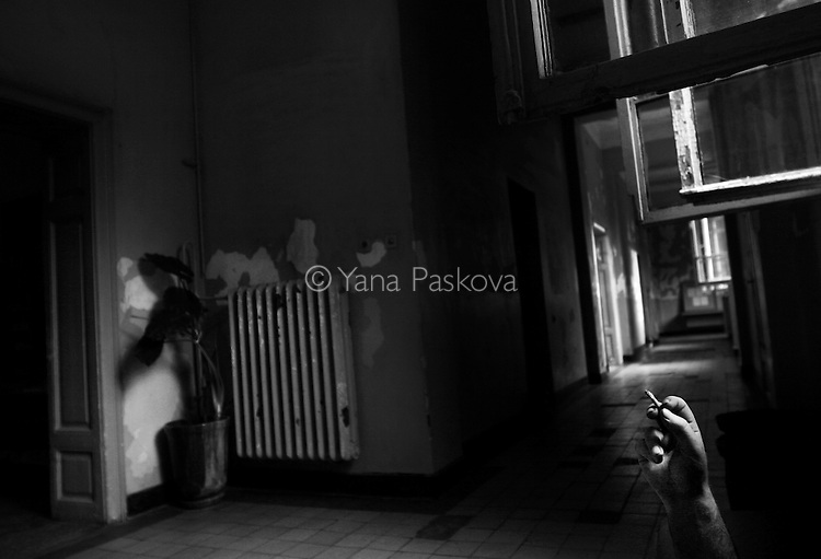 A patient smokes a cigarette in the empty hallway of the psychiatry ward of a county hospital in Bulgaria on August 20, 2007. Coffee and cigarette breaks are amongst the only methods of entertainment and distraction in the ward.
