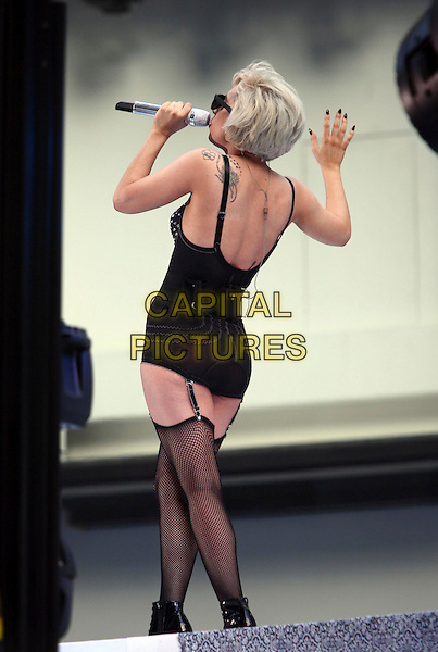 "LADY GAGA (Stefani Joanne Angelina Germanotta).performs live on NBC's the ""TODAY"" Show live from Rockefeller Center, New York, NY, USA, 9th July 2010..music on stage concert gig half 3/4 length  microphone singing  black fishnet stockings basque lingerie body bodysuit knickers sunglasses back rear behind hand tattoos .CAP/ADM/PZ.©Paul Zimmerman/AdMedia/Capital Pictures."