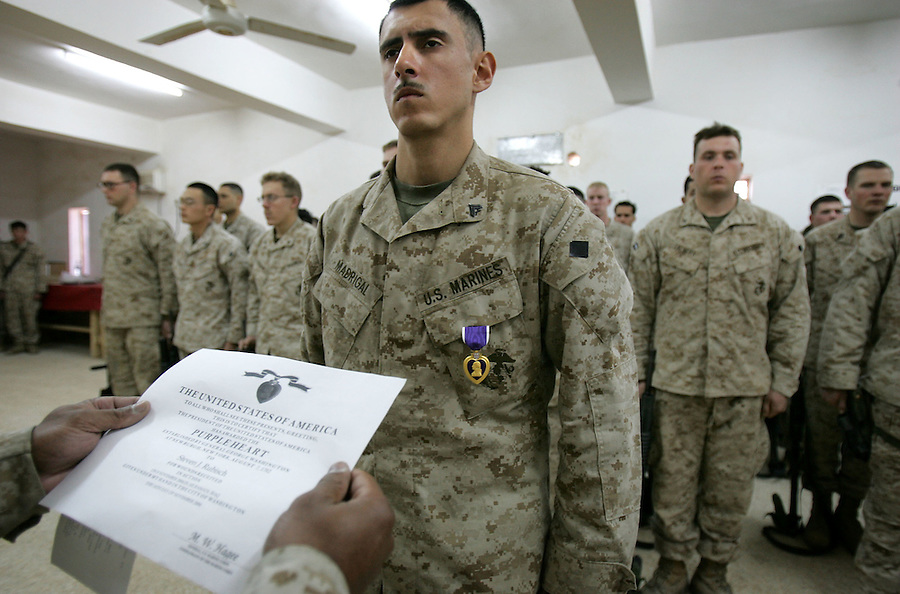 "Cpl. Jose Madrigal, a Marine with 3rd Platoon Echo Company 2nd Battalion 5th Marines, stands at attention with his platoon as he is awarded the Purple Hearts for wounds received in combat (one of three awarded at the ceremony along with an award for valor) during a ceremony at the company's base - the ""Snake Pit"" - on January 9, 2005 in Ramadi, Iraq."