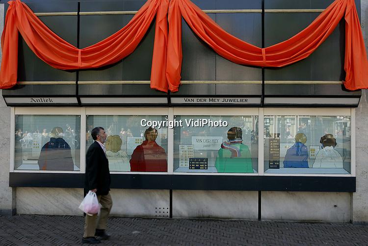 Foto: VidiPhoto..APELDOORN - In Apeldoorn zijn gemeente, brandweer, winkeliers en particulieren maandag begonnen met de aankleding van de stad, in verband met het bezoek van Koningin Beatrix op 30 april. Zo wordt er in de Hoofdsttraat door de gemeente onder meer 50 kilometer aan oranje slingers (kroontjes) opgehangen.