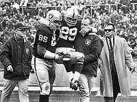 Raiders Howie Williams is carried off the field by Carleton Oats and team trainer George Anderson, also Dick Romanski and team doctor.(1969 photo/Ron Riesterer)