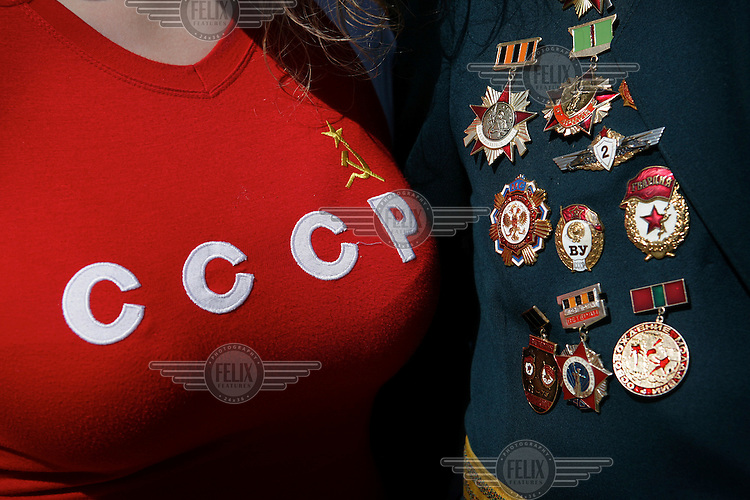 A woman wearing a Soviet style t-shirt stands next to 82 year old WWII veteran Victor Takmir. He is displaying his medals on Moldova's Day of Victory, May 9th, when the country celebrates the victory over Nazi Germany.