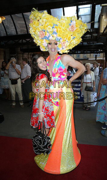 "HAYLEY TAMADDON & CAST MEMBER .""Priscilla: Queen Of The Desert The Musical"" - Cast Change, London, England, UK..June 22nd, 2010.arrivals full length make-up drag queen costume hat character yellow flowers blue dress red floral print tea brown tan shoes peep toe platform black ruffle bag .CAP/WIZ.© Wizard/Capital Pictures."