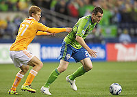 Seattle Sounders FC forward Nate Jaqua, right, tries to escape the grasp of Houston Dynamo defender Hunter Freeman during play between at Qwest Field in Seattle Friday March 25, 2011. The match ended in a 1-1 draw.