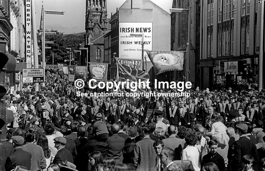 Orangemen taking part in their annual Twelfth Parade march along upper Donegall Street, Belfast, N Ireland, UK, 12th July 1971, passing St Patrick&rsquo;s Roman Catholic Church and the offices of the Irish News newspaper. 197107120557b<br />