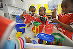 (L-r) Jeremiah Taylor, 3, Daisha White, 4, and Samurai Hoy, 4, play together beside a tub of water and toys in Room 113 at the Educare Early Childhood Center in Chicago on November 21, 2008.  The pre-K daycare center is a model for head start, funded privately by the Gates and other foundations, that cares for and educates infants, toddlers, and 3- and 4-year old pre-school children.