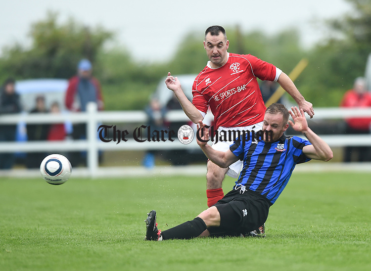 Seamus Lawlor of Newmarket Celtic in action against Chris Lake of Bridge United during their Cup final at Doora. Photograph by John Kelly.