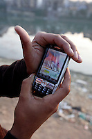 Modasir Ahmad Bhat holds a mobile phone with photage apparently showing the shooting of unarmed protesters by Indian security forces. Srinagar, Kashmir, India. © Fredrik Naumann/Felix Features