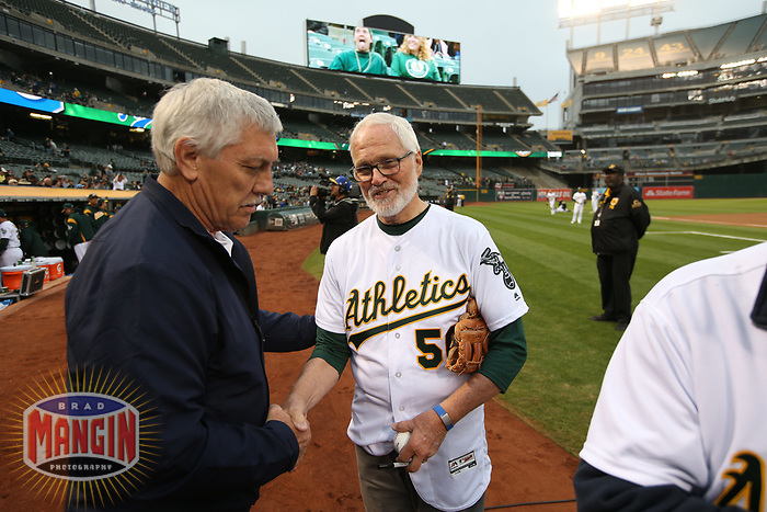 OAKLAND, CA - AUGUST 14:  Photographer Doug McWilliams shakes hands with A's broadcaster Ray Fosse after he threw out a ceremonial first pitch before the game between the Kansas City Royals and Oakland Athletics at the Oakland Coliseum on Monday, August 14, 2017 in Oakland, California. (Photo by Brad Mangin)