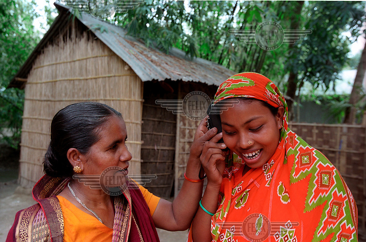 A village woman is talking to her husband from the cell phone of Rabia Begum, who runs a small business where she lets villagers use her cell phone for a nominal fee. Grameen Phone, though not related to Grameen Bank, has a wide network all over Bangladesh. Many women run such small businesses. It has transformed the communication system in rural areas of Bangladesh.  ..