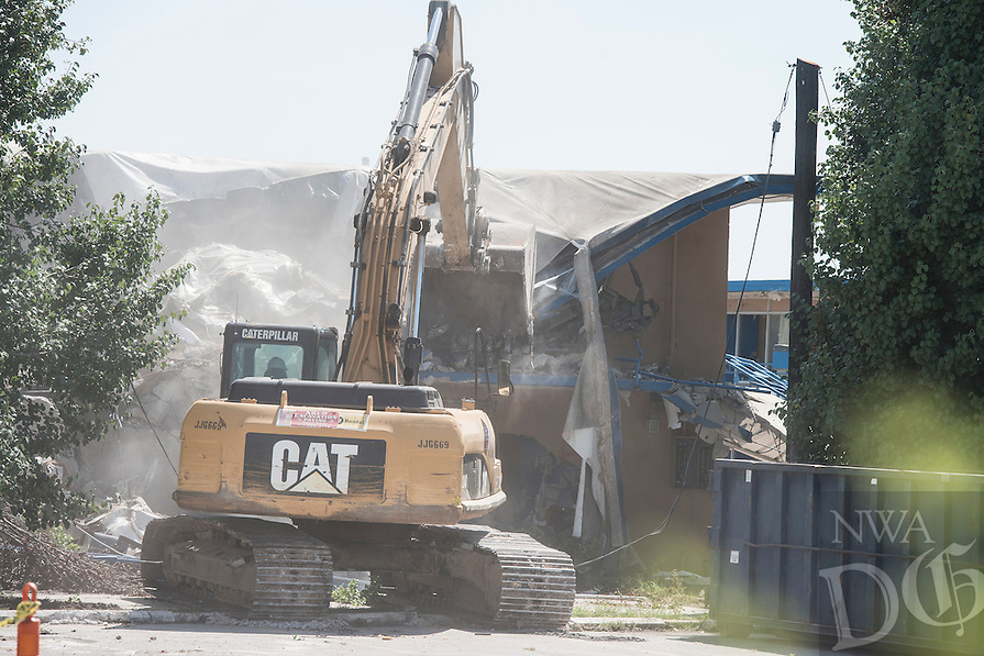 STAFF PHOTO ANTHONY REYES &bull; @NWATONYR<br /> Crews with Arco Excavation and Paving demolish sections of a building Thursday, Aug. 21, 2014 at the site of the former Sunrise Inn in Springdale. The motel was closed for safety reasons and a new CVS pharmacy will be built on the site.