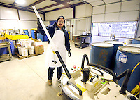 STAFF PHOTO BEN GOFF  @NWABenGoff -- 12/11/14 Victor Sandoval, hazardous waste manager, demonstrates the operation of a bulb crusher at the Benton County Solid Waste District Household Hazardous Waste facility in Centerton on Thursday Dec. 11, 2014. The machine pulverizes fluorescent bulbs and filters out the toxic mercury fumes from the solid material.