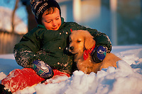 A young boy plays with a Golden Retriever puppy in the snow.